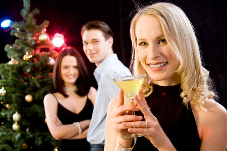 Portrait of beautiful blond woman in her black dress on the background of couple and christmas-tree photo