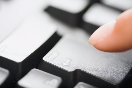 Image of human finger pointing at the enter key on black keyboard photo