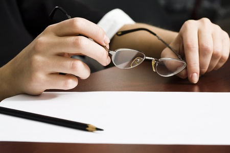 industrious: Sheet of paper and pencil on the desk and human hands holding glasses  Stock Photo