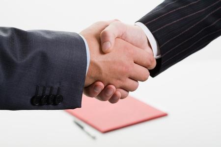 mani che si stringono: Close-up di stringere la mano a fare un accordo sullo sfondo della cartella e penna Archivio Fotografico