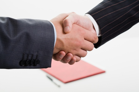 Close-up of shaking hands making an agreement on the background of folder and pen photo