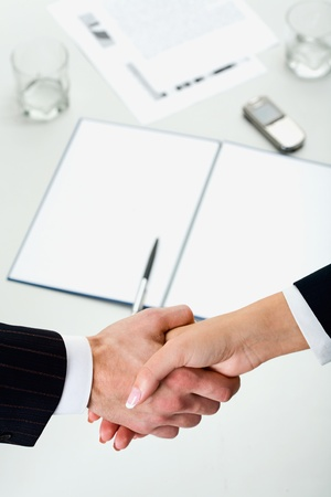 Woman and man shaking hands over paper, pen, phone, glasses on the background photo