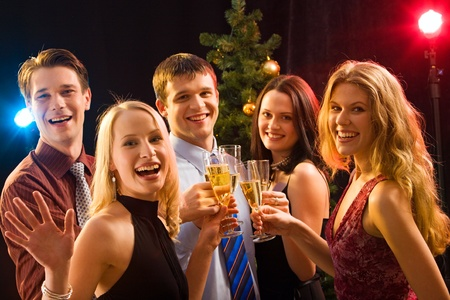 Smiling group of young people enjoying cocktails at christmas photo