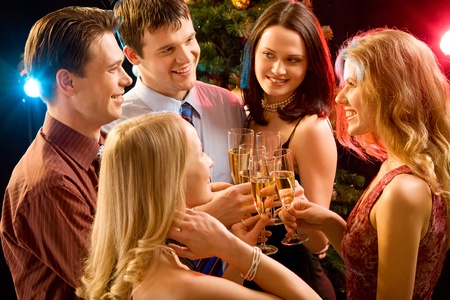 newyear night: Photo of five smiling friends touching their glasses with each other at christmas Stock Photo