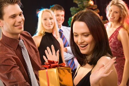 Photo of man giving to pretty woman the present at christmas photo