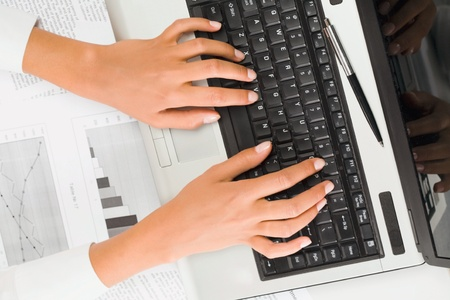 Beautiful female hands typing on the laptop photo