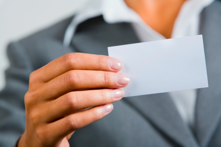 Close-up of female hand holding the white business card photo