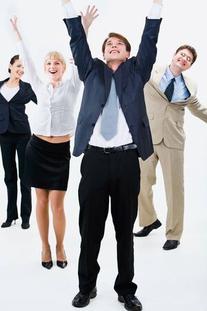 Happy business team are standing and raising hands upwards photo