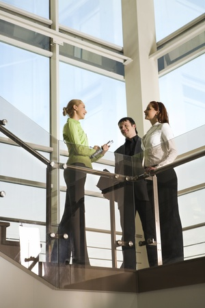 Two girls and man are talking in the building with glassy walls photo