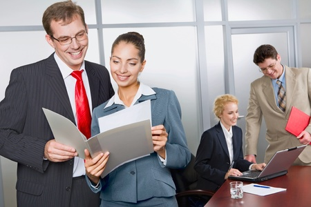 Business woman is showing her successful business plan to a colleague in the office on the background of two business people photo