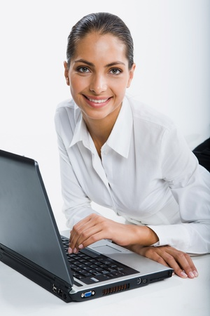 Isolated on white portrait of smiling suntanned woman sitting at the table touching keyboard of opened black laptop gazing at the camera photo