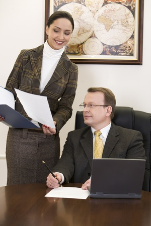 Beautiful woman is showing an official record to the sitting man in the suit photo