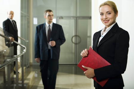 Smart beautiful businesswoman with red case in her hands and two men behind her going downstairs