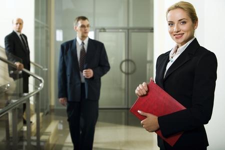 business case: Smart mooie zakenvrouw met rode geval in haar handen en twee mannen achter haar naar beneden gaan
