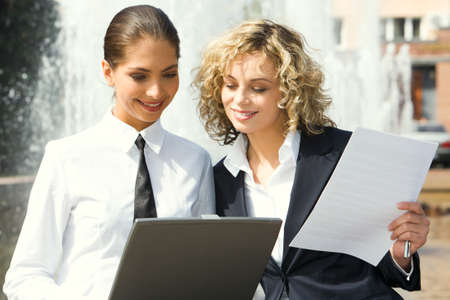 Cute smiling businesswomen reading documents outside and fountain on the background photo