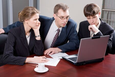 Business team of three professionals looking at monitor of laptop in the office photo