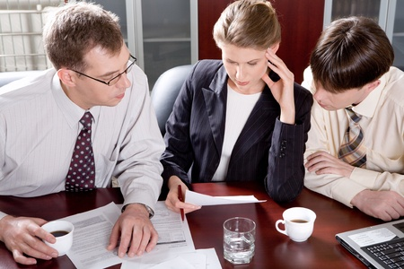 Portrait of professionals sitting at the table and looking at a document Stock Photo - 8393810