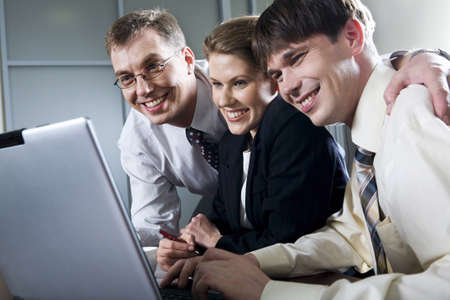 Three smiling businessmen looking at the laptop photo