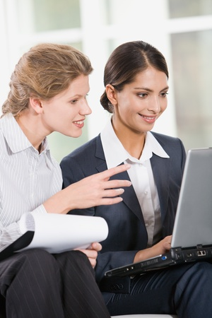 Portrait of two business women looking at the monitor of laptop photo