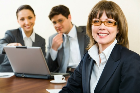 Smart woman in glasses smiles on a background of her the coworkers in the office photo