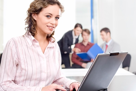 Portrait of beautiful secretary sitting at the table on the background of her co-workers Stock Photo - 8357342