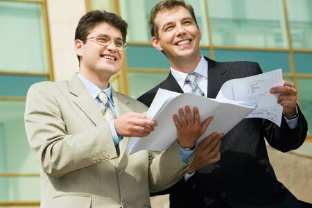 Two businesspeople holding papers looking towards and business center with glassy walls on the background  photo
