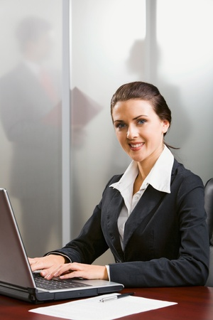 Outstanding smiling specialist is typing on the laptop in the office photo