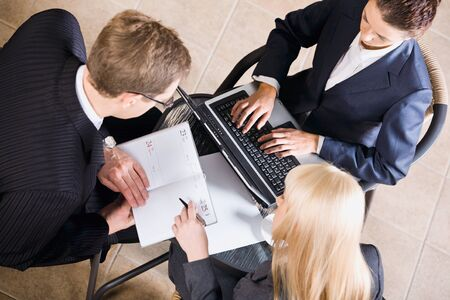 Businesspeople gathered around a table for a meeting and brainstorming Stock Photo - 8393739