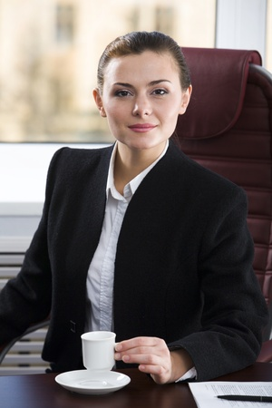 Smart sensual businesswoman is coffee on her workplace photo