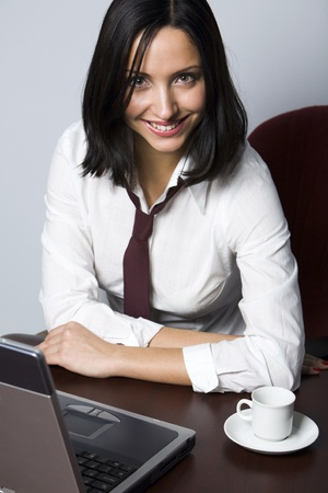 Smiling Hispanic brunette drinking coffee in front of her lap top  photo
