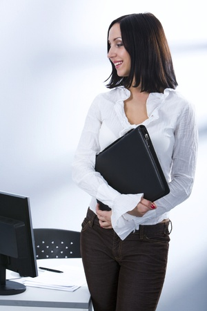Smiling businesswoman standing near her workplace with the document case in her hands looking at the monitor photo