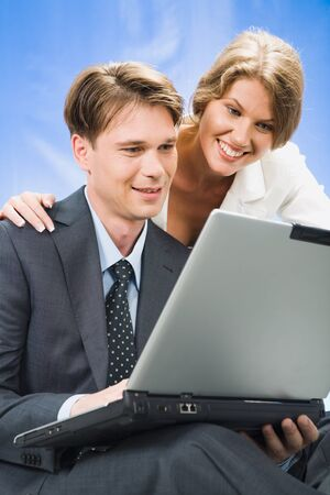Young woman looks in the laptop with her colleague  photo