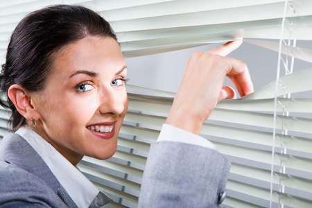 Young pretty woman looking through white jalousie photo