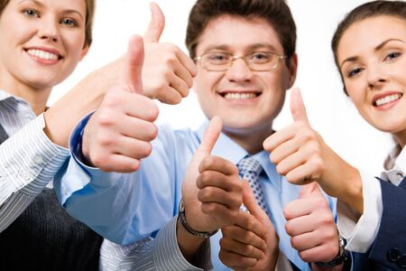 Team of three office workers give the thumbs up sign photo