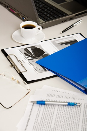 Business documents, laptop, eyeglasses, pens, folder and cup of coffee are lying on white table photo