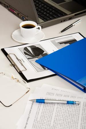 daily room: Documenti aziendali, portatile, occhiali, penne, cartella e caff� sono distesi sul tavolo bianco