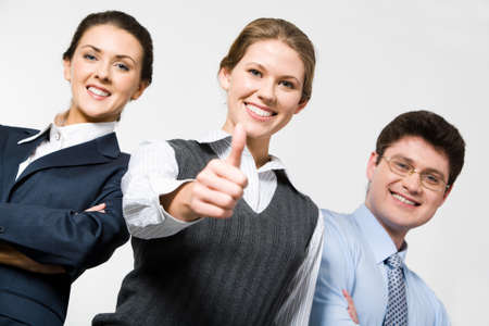 Smiling woman demonstrates thumb up with business people  photo