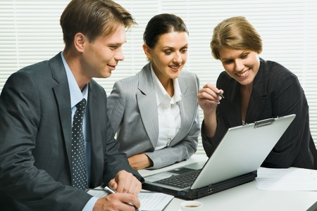 Business woman is explaining the correct way of analysis to her colleagues in  the office  photo