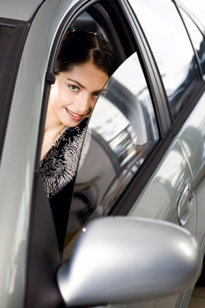 Portrait of vivid brunette looking with interest through the window of her car    photo