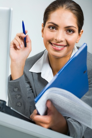 Portrait of smiling business women holding the pen, blue folder and papers in a room photo