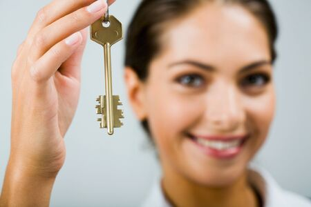 Smiling business woman is holding the key photo
