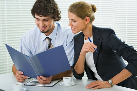Portrait of businesspeople sitting at the table and reading paperwork photo