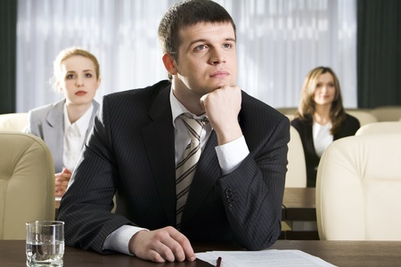 Portrait of boring man sitting at the table and two women on the background photo