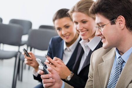 Portrait of young businesspeople exchanging an information on the mobile phones Stock Photo - 8393712