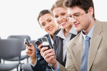 Portrait of young businesspeople sharing info on mobile phones in the room  photo