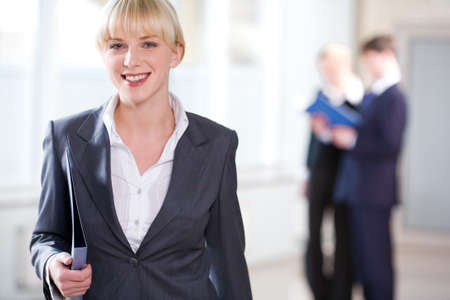 Portrait of young business woman holding a folder on the background of people Stock Photo - 8357351