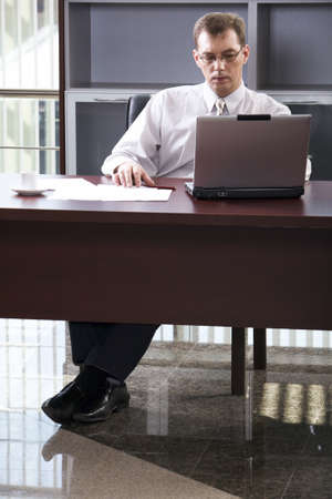 Smart businessman seating comfortably at the table working on his lap top at the office photo