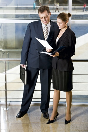 Businesswoman showing documents to her colleague in the building with glassy walls Stock Photo - 8393733
