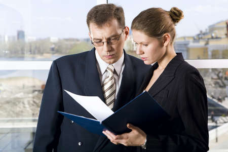 Portrait of two businesspeople reading documents with concentration photo