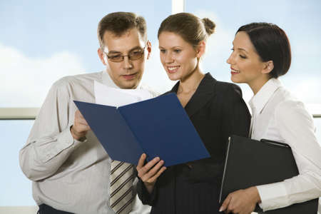 Smiling young woman showing documents to her boss and cuus girl looking into the paper case Stock Photo - 8393445